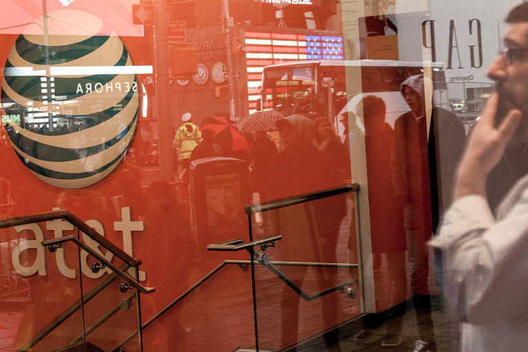 An AT&T store window in New York. The proposed AT&T-Time Warner merger and others of that scale are reconfiguring the American economy in ways that seem tilted against workers. Credit George Etheredge for The New York Times